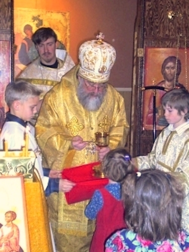 Archbishop BENJAMIN serves Communion to parish children.