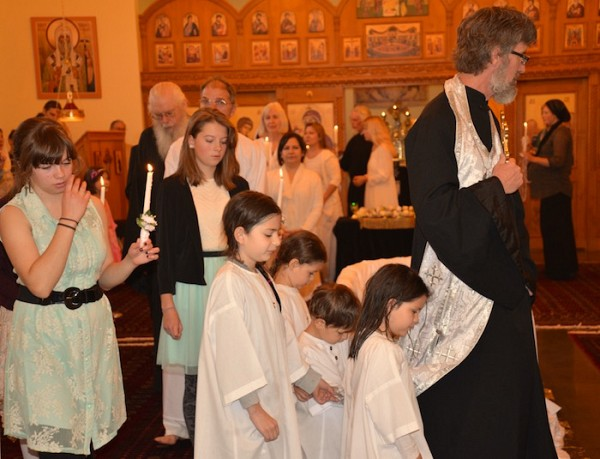A procession of the newly baptized and chrismated and their sponsors.