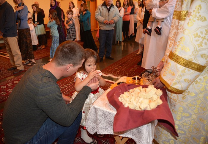 A child participates in the Liturgy with the help of her godfather.