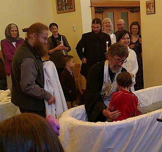 A child is baptized into Christ.